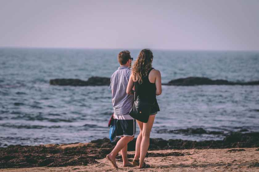 woman and man walking near seashore