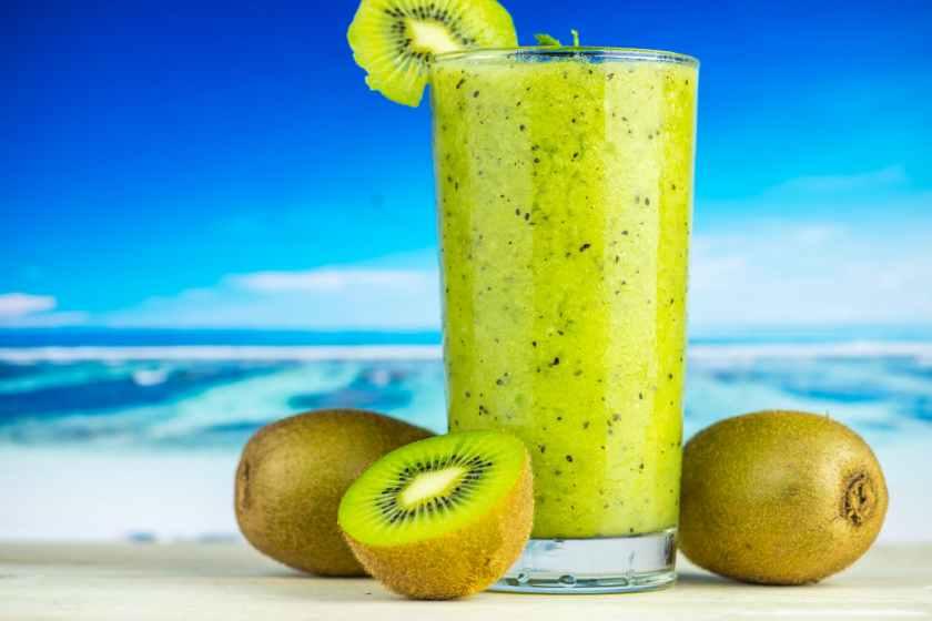 kiwi fruit beside drinking glass filled with kiwi shake